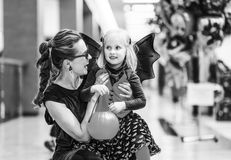 Smiling elegant mother and daughter on Halloween at mall. Trick or Treat. Portrait of smiling elegant mother and daughter in bat costumes on Halloween at the Stock Images
