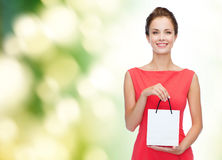 Smiling elegant woman in dress with shopping bag Stock Photo
