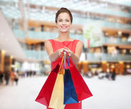 Smiling elegant woman in dress with shopping bags Royalty Free Stock Images