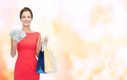 Smiling elegant woman in dress with shopping bags Royalty Free Stock Photography