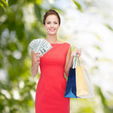Smiling elegant woman in dress with shopping bags Stock Images