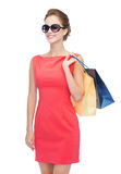 Smiling elegant woman in dress with shopping bags Royalty Free Stock Image
