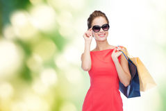 Smiling elegant woman in dress with shopping bags Stock Image