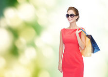 Smiling elegant woman in dress with shopping bags Royalty Free Stock Photos