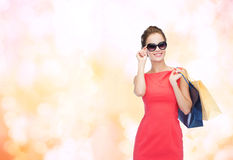 Smiling elegant woman in dress with shopping bags Stock Photo