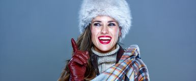 Smiling elegant woman in fur hat  on cold blue got idea. Winter things. Portrait of smiling elegant woman in fur hat  on cold blue got idea Stock Image
