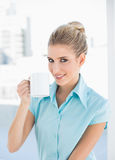 Smiling elegant woman holding coffee. In bright office Royalty Free Stock Images