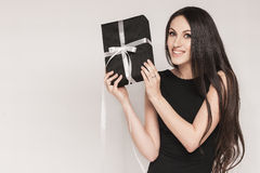 Smiling elegant woman holding gift. Young beautiful woman with long hair wearing black cocktail dress is holding elegantly wrapped gift Royalty Free Stock Photography