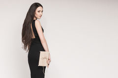 Smiling elegant woman holding gift. Young beautiful woman with long hair wearing black cocktail dress is holding elegantly wrapped gift Stock Photography
