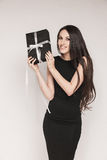 Smiling elegant woman holding gift. Young beautiful woman with long hair wearing black cocktail dress is holding elegantly wrapped gift Royalty Free Stock Photos