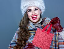 Smiling elegant woman holding small red shopping bag. Winter things. smiling elegant woman in fur hat isolated on cold blue background holding small red shopping Stock Photo