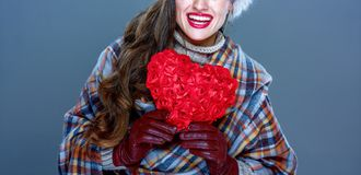 Smiling elegant woman isolated on cold blue with red heart. Winter things. Closeup on smiling elegant woman in fur hat isolated on cold blue with red heart Stock Images