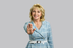 Smiling elegant woman making gesture stop. Joyful mature businesswoman gesturing stop sign while standing isolated on grey background Royalty Free Stock Photography