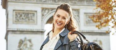 Smiling elegant woman near Arc de Triomphe in Paris, France. Stylish autumn in Paris. Portrait of smiling young elegant woman in trench coat near Arc de Triomphe Stock Photo