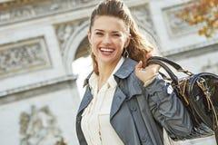 Smiling elegant woman near Arc de Triomphe in Paris, France. Stylish autumn in Paris. smiling young elegant woman in trench coat near Arc de Triomphe in Paris Stock Photography