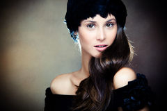 Smiling elegant woman portrait. Young elegant woman wearing feather hat portrait, studio shot Royalty Free Stock Images