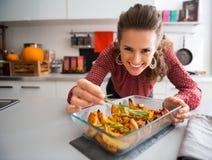 Smiling elegant woman preparing roasted pumpkin dish Royalty Free Stock Photos