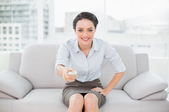 Smiling elegant woman with remote control sitting on sofa Royalty Free Stock Photography