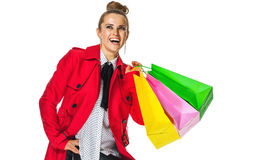 Smiling elegant woman shopper on white looking on copy space. Keep the autumn bright. Full length portrait of smiling elegant woman in red coat isolated on white Stock Image