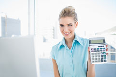 Smiling elegant woman showing calculator. In bright office Stock Photo