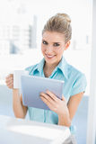 Smiling elegant woman using tablet holding coffee. In bright office Royalty Free Stock Image