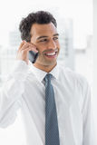 Smiling elegant young businessman using cellphone Royalty Free Stock Photography