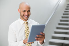 Smiling elegant young businessman using digital tablet Royalty Free Stock Photography