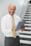 Smiling elegant young businessman using digital tablet Stock Photos