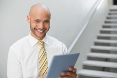 Smiling elegant young businessman using digital tablet Royalty Free Stock Photos