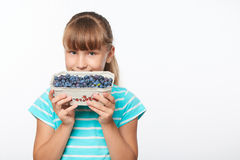 Smiling elementary school age girl. Smiling girl holding a box with bilberries, over white background Stock Image