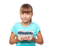 Smiling elementary school age girl. Smiling girl holding a box with bilberries, over white background Royalty Free Stock Image