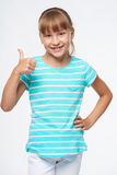 Smiling elementary school age girl showing thumb up Stock Photo