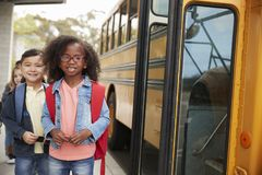 Smiling elementary school kids queueing for the school bus royalty free stock photo