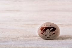 Smiling emoticon with sunglasses. Stone face on white wood background with free space for your text Stock Images