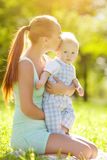 Smiling emotional kid with mum on a walk. Smile of a child. Cute little baby in summer  park with mother  on the grass. Sweet baby and mom  outdoors. Smiling Royalty Free Stock Photo
