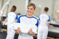 Smiling employed holding clean and ironing textiles Royalty Free Stock Photo