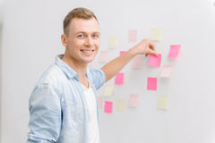 Smiling employee is busy with post-it notes Stock Photos