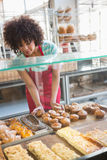 Smiling employee moving over the pastry Royalty Free Stock Photography