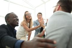 Smiling employees giving each other a high five. The concept of teamwork royalty free stock photography