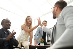 Smiling employees giving each other a high five. The concept of teamwork royalty free stock images