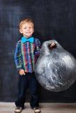 Smiling encoureged redhead school-boy holding huge Royalty Free Stock Image
