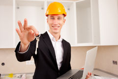 Smiling engineer gives keys Royalty Free Stock Image