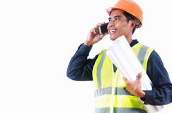 Smiling engineer holding blueprint talking on the phone Royalty Free Stock Photos