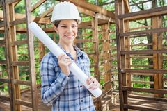 Smiling Engineer Holding Blueprint In Wooden Cabin Stock Images