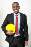 Smiling engineer holding a hard hat Royalty Free Stock Photo