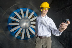 A smiling engineer, looking at his phone. Inside the realms of an industrial windtunnel Stock Image