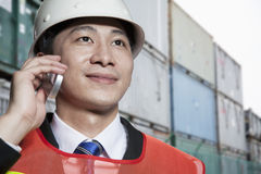 Smiling engineer in protective workwear on the phone in a shipping yard Stock Image