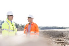 Smiling engineers discussing at construction site on sunny day Stock Image