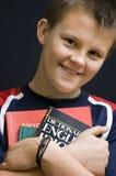 Smiling English student. Portrait of a teenage boy holding his English language books, smiling. Black background portrait Royalty Free Stock Photo