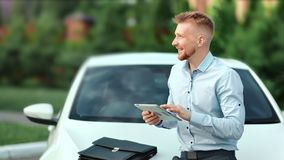 Smiling enthusiastic male businessman using tablet pc outdoor at car background medium shot. Happy casual successful young man enjoying digital display stock video